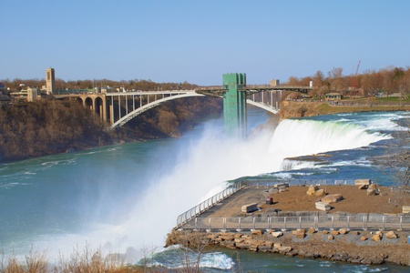 Niagara Falls pours into the river  This wonder of the world is located near the Rainbow Bridge which is seen in the distance   Stock Photo