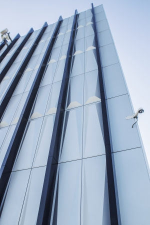 Tall building with a shining silver design  Shot is taken from a low perspective and steep angle  There is a security camera on the lower edge