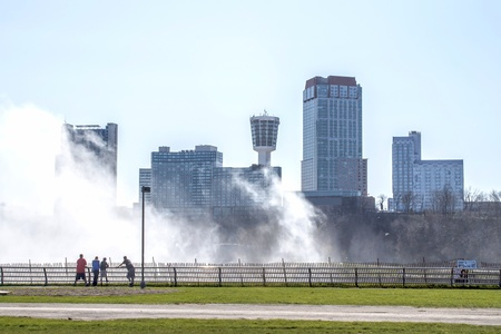 Shot of Niagara Falls Ontario from the American side  Mist from Niagara Falls hangs in the air around interestingly designed buildings  There is a group of young men at the viewing railing
