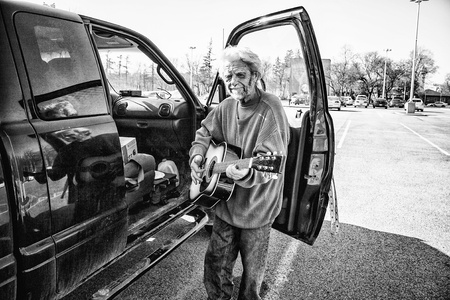 Weathered bearded older man with his guitar