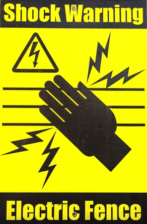 electric fence: Warning sign on an electric fence in bright yellow
