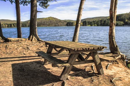 An empty wooden table sits on a wooded island in the middle of a mountain lake. This shot has beautiful natural lightning.  Stock Photo