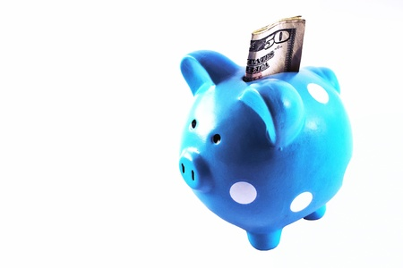 fifty dollar bill: Blue piggy bank sits on white background. The item has white spots and a US fifty dollar bill peeking out. Stock Photo