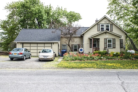 arge two story home with garage and new roof. Two compact cars are in the wide driveway. Tulips are overpowering the landscaping.  Stock Photo