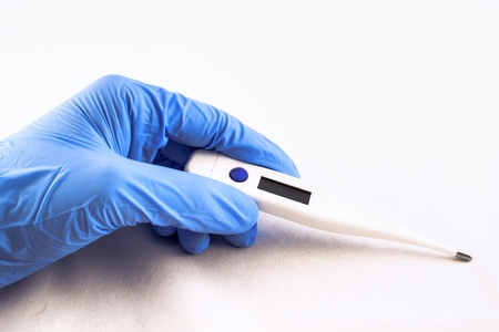 Hand donned in blue latex glove displays an electric thermometer.  Stock Photo