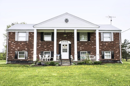 Big brick raised ranch style home with white pillars and fresh landscaping Stock Photo - 19608219