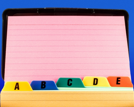 Close shot of a blank pink index card propped up against file box tabs  The background is a rich blue