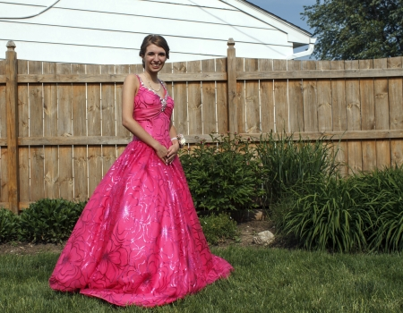 Girl poses outside in her beautiful pink prom dress. Stock Photo