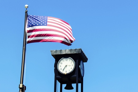 American flag flaps in the wind next to a clock tower