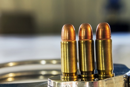 Three handgun bullets positioned on top of handcuffs