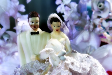 topper: Close up of old time wedding cake topper  Groom and bride are positioned in front of beautiful purple flowers