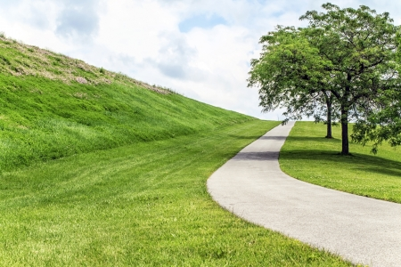 Paved footpath up a grassy hill   Stock Photo
