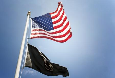 prisoner of war: Flying United States flag and Prisoner of War flag flapping in the wind  Stock Photo