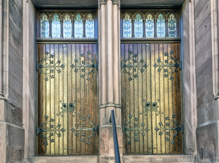 Wooden church doors with beautiful iron work and glass windows   Stock Photo