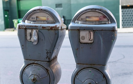 Old, rusty, and broken parking meters on the road