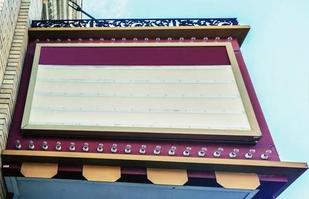 Blank retro cinema billboard hanging from a building