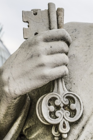 Stone hand delicately holds keys of intricate design.