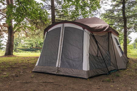roughing: Tan and modern family tent set up under the pines  Zippered door and metal poles