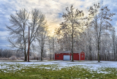 Winter scene of ice covered trees and barn  The sky is cloudy at sunset