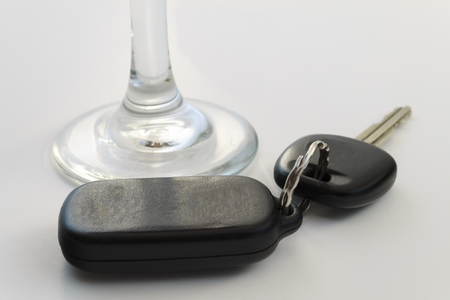 Black car keys and stem of a wine glass