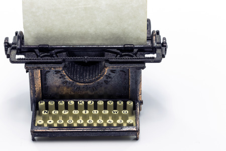 collectable: Close view of bronze typewriter collectable  Blank paper on roll