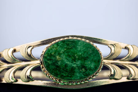 Green gemstone set inside a shiny gold band