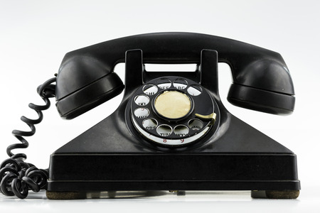old telephone: Surface level view of old black rotary dial phone