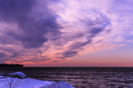 hued: Lake with frozen shoreline and beautiful pink sunset with wispy purple hued clouds