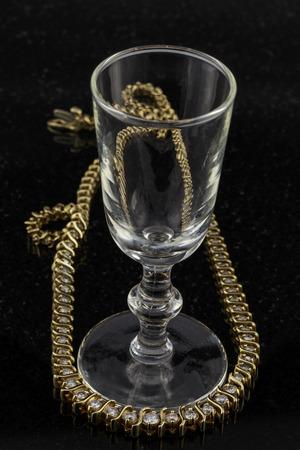 Wine glass with diamond necklace on shiny back surface.