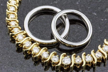 Titanium wedding bands and diamond necklace on black marble