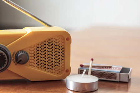 Storm supplies  Wind up weather radio with candle and matches