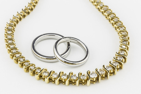 titanium: Two silver titanium wedding bands with gold necklace  All on white background   Stock Photo