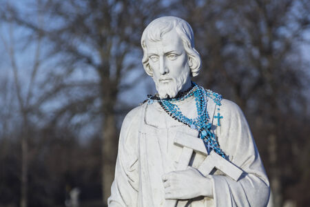 Stone statue of Catholic Saint with blue rosary beads