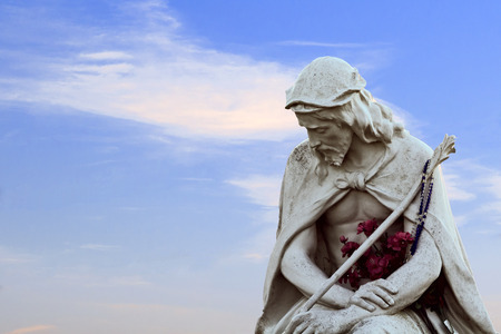 Sorrowful jesus statue with flowers on a blue sky with wispy clouds