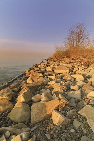 Golden sunset tones light the rocky coastline of Lake Ontario