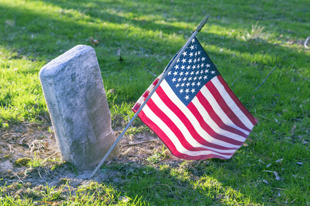 United States of America flag stuck in the ground at a soldiers grave