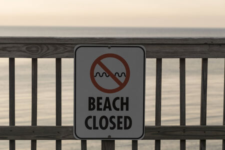 Beach is closed sign posted on wooden pier. Calm waters in the background.  Stock Photo