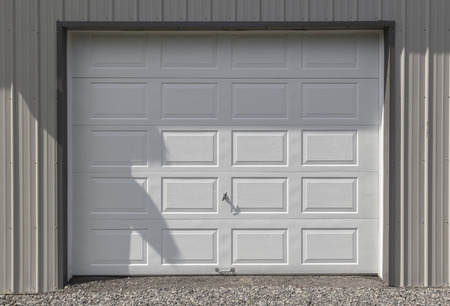 Clean and crisp white metal garage or barn door. The siding is light grey.  Stock Photo