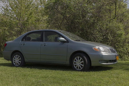hubcaps: Four door compact car in green. Made in 2005. Parked in a grass yard.