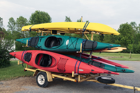 Trailer full of six colorful one man kayaks in a parking lot.  Stock Photo