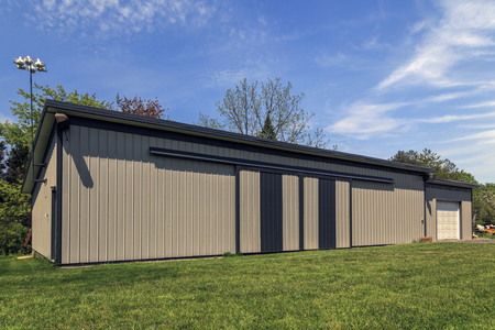 Long steel and modern barn with closed sliding doors and garage addition. Blue sky in the background.  Stock Photo
