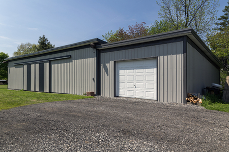 Large grey steel barn in modern style. White garage door with gravel driveway.  Stock Photo