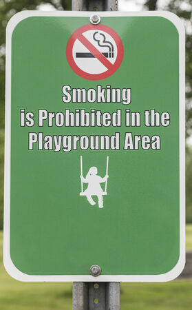No smoking in the playground area sign. Icon of child swinging.   Stock Photo