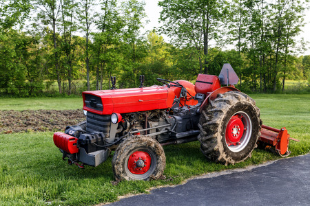 Red tractor with cultivator attached. Parked after just finishing a garden.  Stock Photo