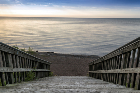 Wide wooden stairway to small beach on the lakefront. Calm water and sky in the background.