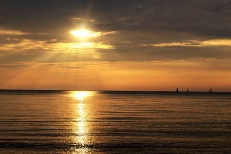 Orange sparkling sun shines through the clouds and reflects onto calm water. Sailboats in the far distance.