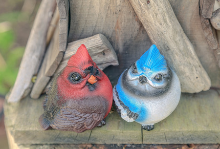 Cartoon style cardinal and bluejay statue on top of a wooden birdhouse.