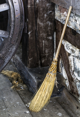 Old fashioned hand crafted straw broom propped up against wall.