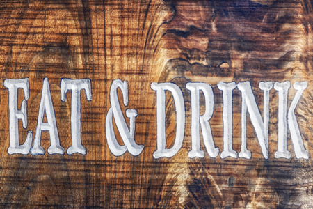 Old time wooden tavern sign with eat and drink printed.