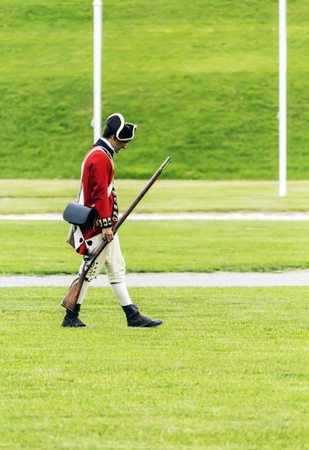 British soldier dressed in historic red coat garb walks across the yard with head held low.